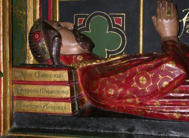 A tomb with a carving of a man resting his head on three books