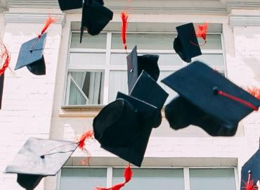 Graduation caps being tossed into air