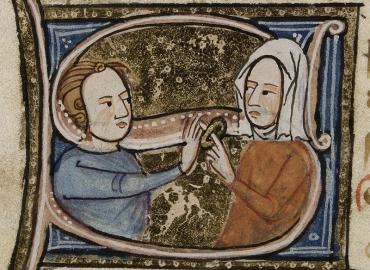 """A decorated letter """"S"""" with miniatures of a man putting a ring on a woman's finger"""