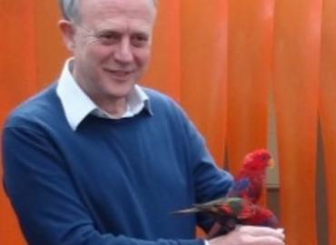 Christopher Martin holding a bright red bird